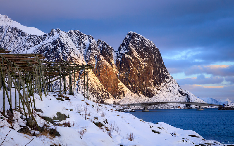 Sunlit peaks and fisherman's drying racks - view from the village of Reine in Norway's Lofoten archipelago.