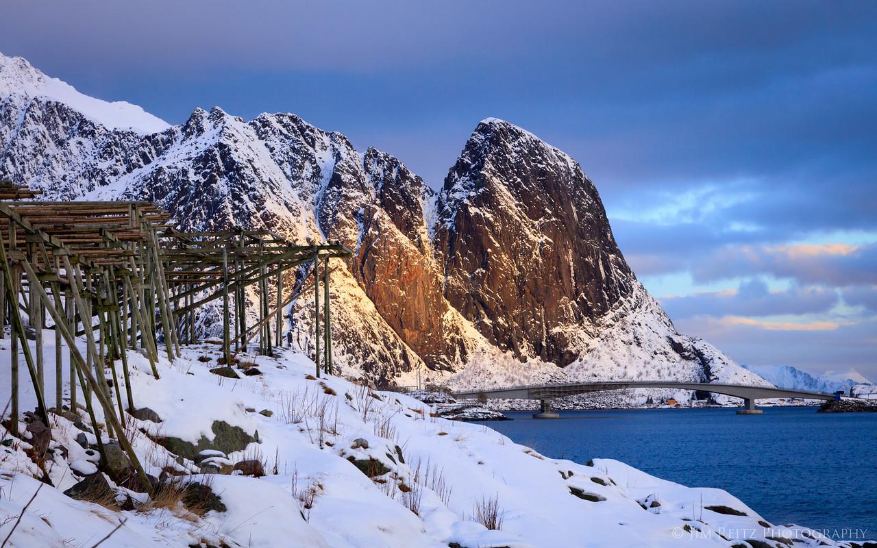 Sunlit peaks and fisherman's drying racks - view from the village of Reine in Norway's Lofoten archipelago.