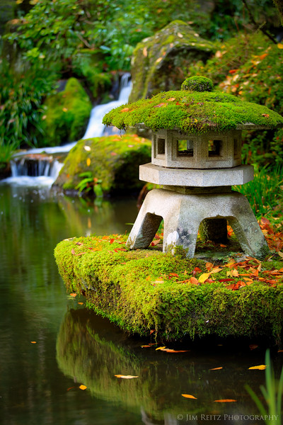 Stone lantern, reflection, and waterfall at the Portland Japanese Garden.