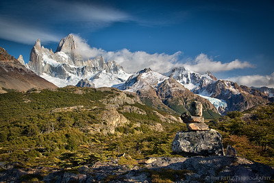 Mount Fitz Roy finally reveals itself without clouds. Some hikers left the rock cairn in the foreground.
