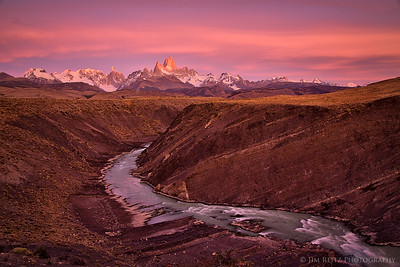 Gorgeous pink and orange glow over Mount Fitz Roy and the Rio del las Vueltas canyon at sunrise.
