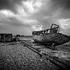Dungeness is a headland on the coast of Kent, England, formed largely of a shingle beach in the form of a cuspate foreland. It shelters a large area of low-lying land, Romney Marsh.