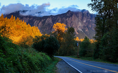 Sunset light falls on a narrow strip of trees, with Mount Si in the background.