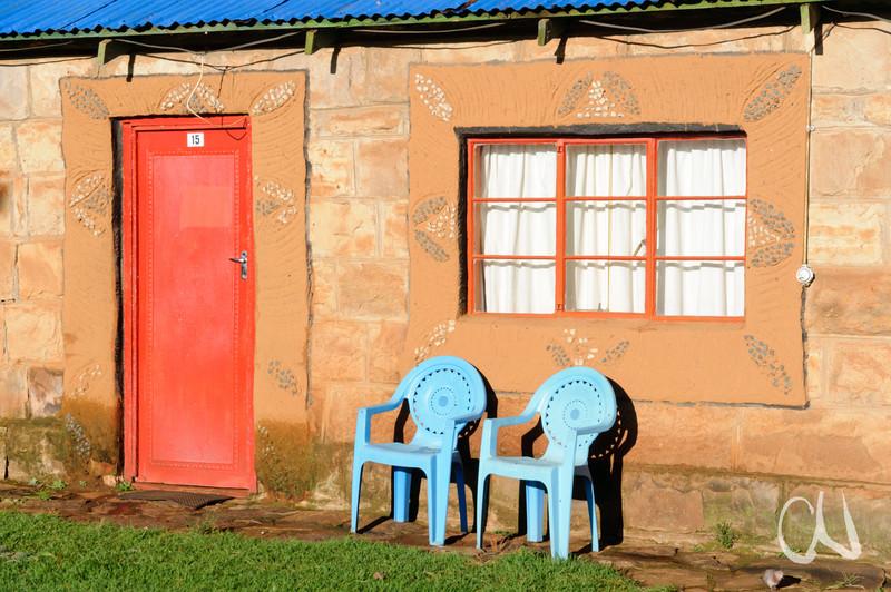 zwei blaue Stühle vor einer Steinhütte mit roter Tür und Fenster, Malealea-Lodge, Lesotho