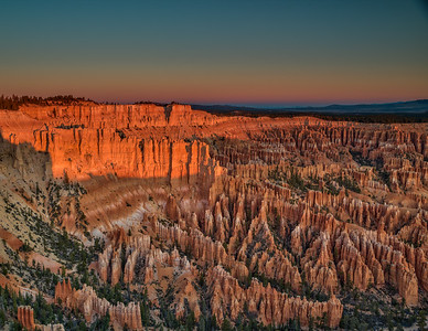 "Sunrise creeps over the horizon and lights up the ""hoodoos"" in Bryce Canyon."