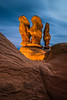 Devils Light<br /> <br /> Midst the darkness of night, the moon lights up the clouds overhead causing the sky to illuminate, while large rock formations tower in Grand Staircase National Monument. <br /> <br /> With carefully placed lighting, the rocks radiate with a warm glow in Devils Garden.