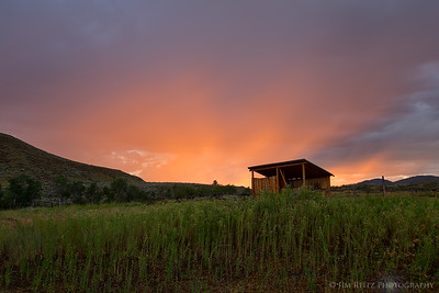 Salmon-colored sunset behind the cabin.
