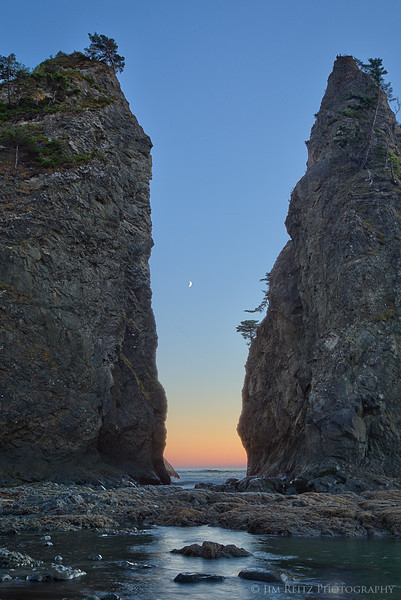 The moon sets between sea stacks on Rialto Beach