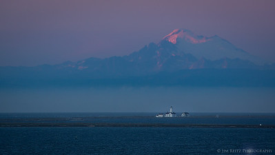 The New Dungeness Lighthouse sites at the far end of 5-mile long Dungeness Spit. Mount Baker in the background.