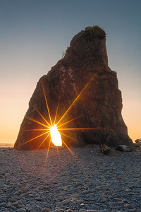 """Sea stack with sun star - say that 5 times fast :-)  This is the first small sea stack rock you see at the entrance to Ruby Beach in Olympic National Park. The sun star is an old-school """"analog"""" trick: set your aperture as small as possible - f/22 in this case - and the lens diffraction will create these cool ray-shaped light flares."""
