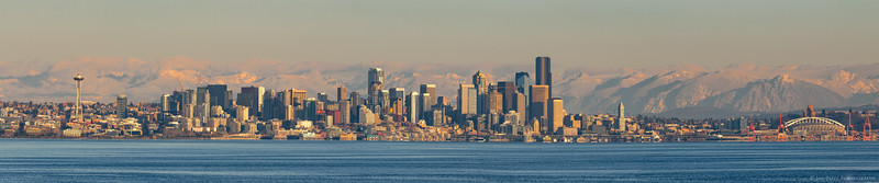Wide-angle panorama of downtown Seattle with snowy Cascade mountains in the background. Taken from Bainbridge Island ferry.