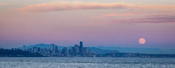 Full moon rising over Seattle at sunset.