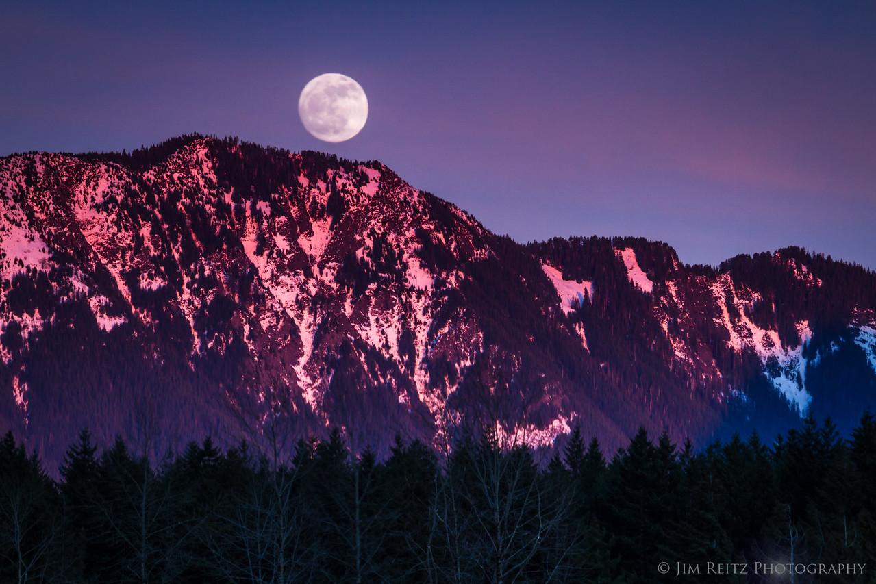 Moonrise at Rattlesnake Lake as nearby Mailbox Peak lights up with alpenglow - near North Bend, WA.