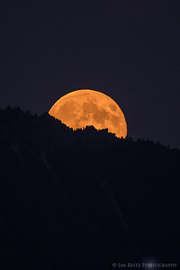 The full moon peeks above the crest of Mount Si.