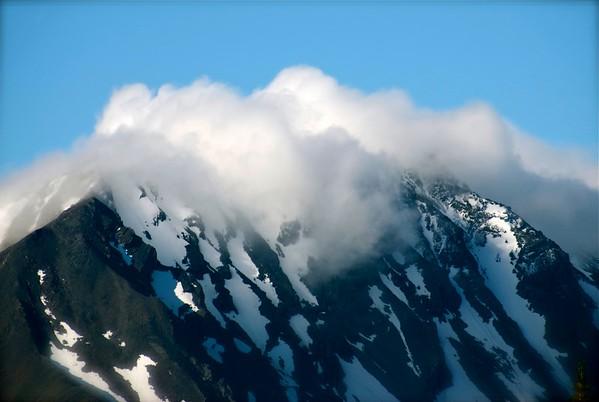Clouds on top of Alaska mountain,snow.