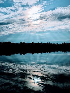 Sunrays through clouds with reflecton in lake
