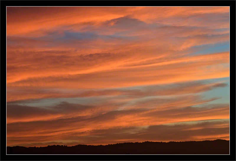 Striped Clouds at Sunset  The sun has set below the Santa Cruz mountains, but the last light gives a warm glow to the layered clouds.  San Francisco Bay Area California  17-AUG-2011