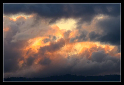 Backlit Clouds Breaking  The last light of sunset peeks through low clouds over the Santa Cruz mountains.  San Francisco Bay Area California  21-NOV-2011