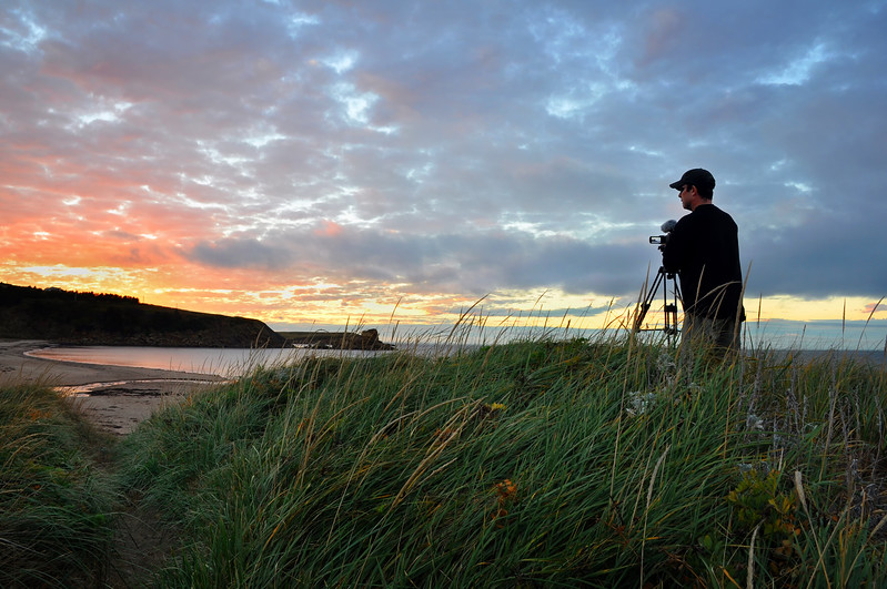 Videographer shooting the setting sun, Margaree Harbour, Nova Scotia