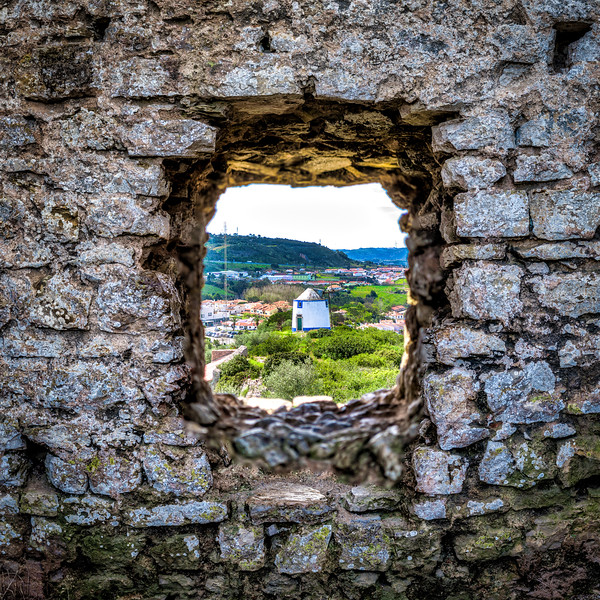 A view through the city wall of Obidos on a windmill.