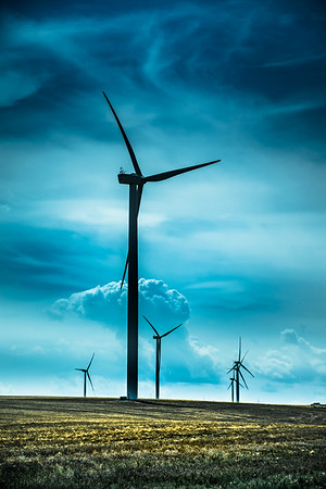Electric turbines in vast field against deep blue sky and clouds in Idaho, USA.