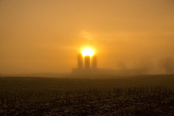 Heavy fog  and sunrise above the triple silos