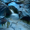Evergreen trees reflected off a pool of water on the the Blur Rock Creek. depending on how the light hits the rocks the blue case of the rocks will be subtle or very strong. To take this photo I wanted to rocks to be wet and reflective so I brought out a water pitcher and scooped up water from the creek and splashed the rocks with the creek water.