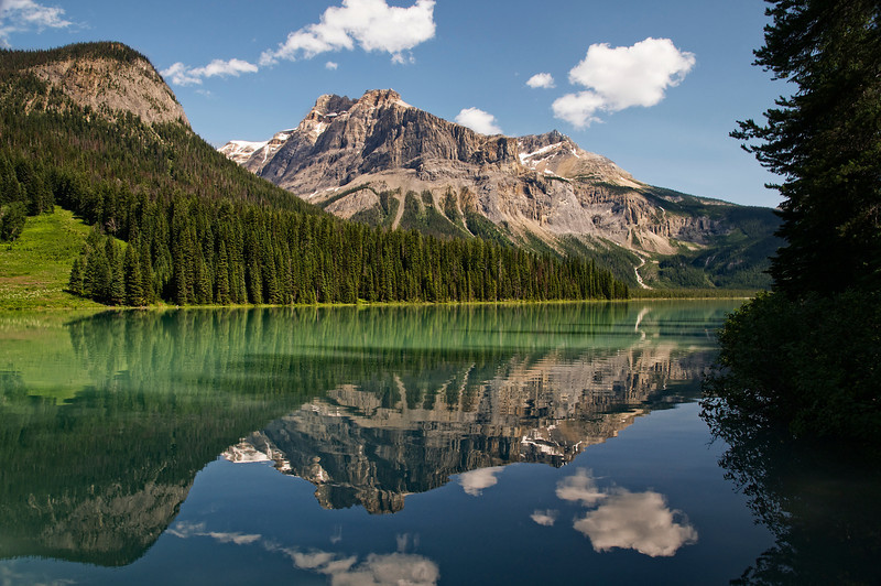 Reflections off theEmerald Lake of the mountains and what look like smoke signals coming from beyond the mountains.