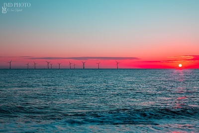 Crimson dawn. Clean energy offshore wind farm turbines at sunrise