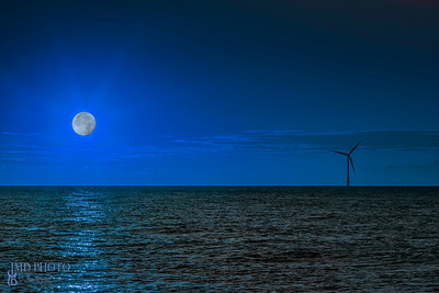 Wind turbine at night with moonlight over the sea