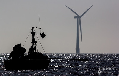Sustainable resources. Small fishing boat infront of offshore wind turbine.