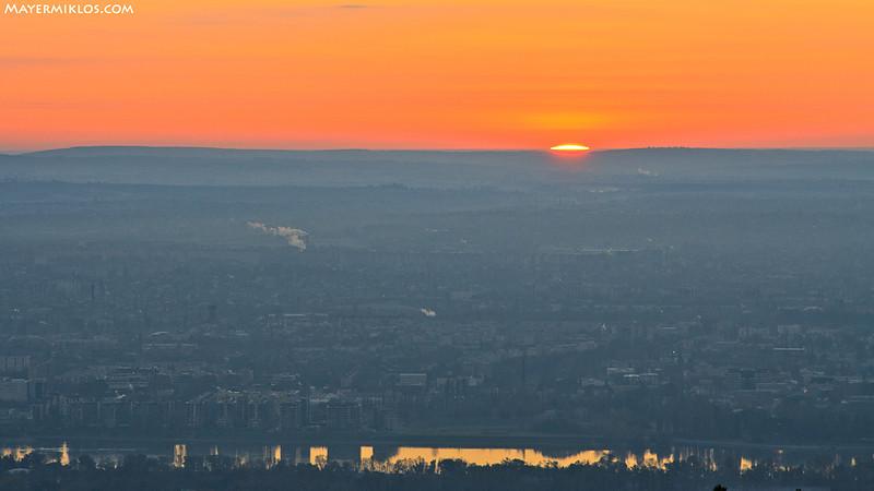 Napkelte Budapest felett, alul balra a Marina part.