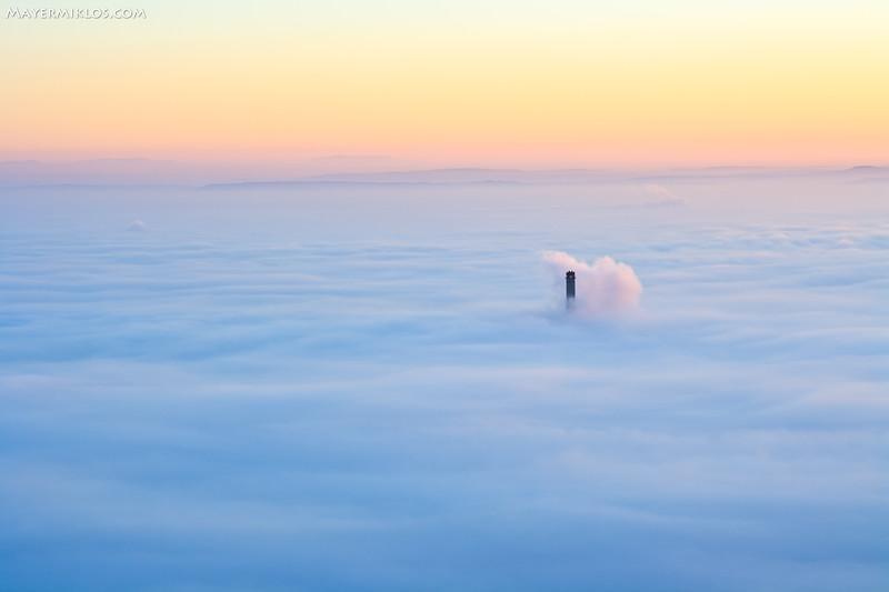 The 203 meters high chimney of a thermal power station is just above the clouds in Budapest at the time of sunrise.  Az óbudai erőmű kéménye (203m magas) éppen kilóg a Budapestet teljes egészében beborító ködből.