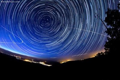 Startrails from Dobogókő. Looks like a vortex! :) Inside the whole, exactly in the middle of the startrail circles is the north pole, and just under that the Polaris. You can see that certain stars never set behind the horizon, they are called circumpolar (for example the Big Dipper or Cassiopeia). That illuminated line at the bottom is the Danube.  Így fordulnak körbe a csillagok Dobogókő felett! A körök középpontja adja ki északi sark metszépontját az égen, alatta picivel helyezkedik el a Sarkcsillag. Jól látszik, hogy az északi sarktól bizonyos távolságon belül eső csillagok soha nem nyugszanak le, őket hívjuk cirkumpolárisnak. Nálunk ilyen pl. a Göncölszekér vagy a Cassiopeia csillagai. A kép jobb felében fut a Tejút. A felvétel 225 db expozicíó összerakásából született, kb. 2 órát ölel át. Alul a fénycsík a Dunakanyart jelzi.