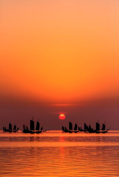 Junks at sunrise over moon bay, Huzhou, China.  Lake Tai