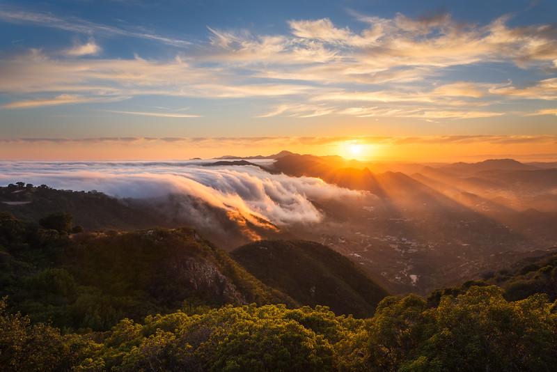 Fog and sun rays over Malibu at sunset