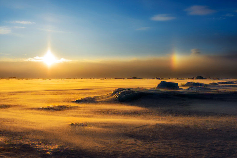 """Early morning light and a """"sun dog"""" over the frozen Bering Sea, Nome, Alaska."""