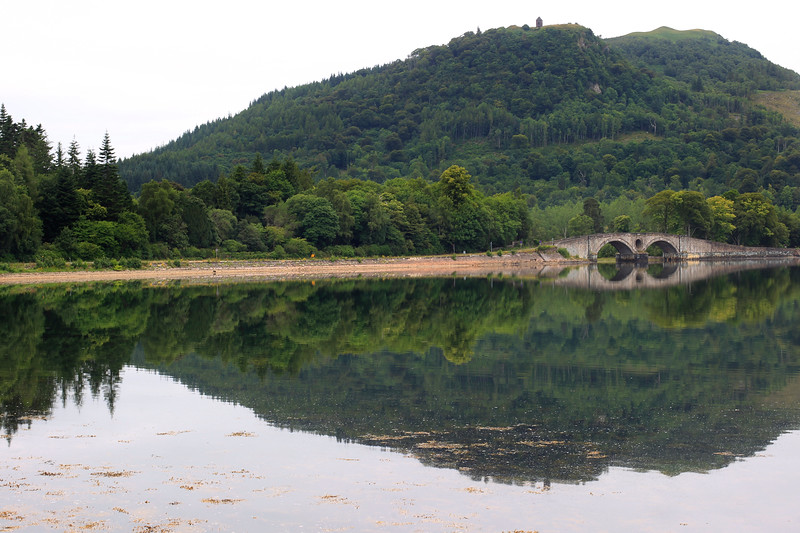 A hill is reflected in Loch Fyne at Inverary, Scotland. Photo by Doug Oakley