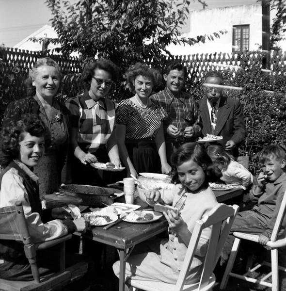 At table: Gladys, Linda, Steve. Standing: Grandma Pekow, Mom, Sally, Ben, Harry Pekow