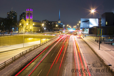 Light trails on Lyndale Avenue taken from the pedestrian bridge linking the Minneapolis Sculpture Garden and Loring Park. The Walker Art Museum is on the right