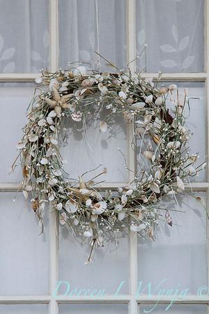 Seashell wreath hanging on a window_2340