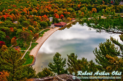 West Bluff Trail Hikers' enjoy blazing autumn foliage and a glassy Devils Lake reflecting skies within Devils Lake State Park (USA WI Baraboo)