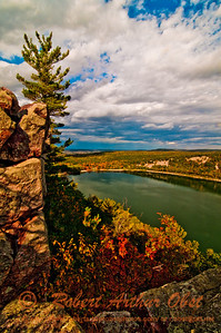 Hikers enjoy gorgeous autumn foliage and cliffs under moody skies along the West Bluff Trail within Devils Lake State Park (USA WI Baraboo)