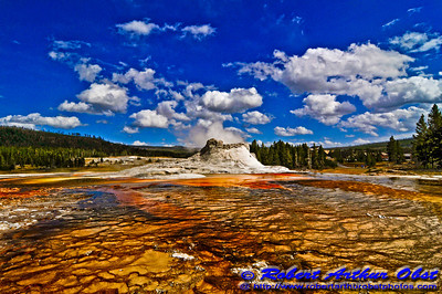 Cerulean skies and vibrant colors frame smoking Castle Geyser within Yellowstone National Park (USA WY YNP)