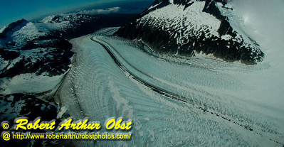 Ambitious hikers and ice climbers and float plane or helicopter riders may enjoy blue sky views of remote snowy mountains and flowing rivers of ice from near the top of twelve miles long Mendenhall Glacier within Tongass National Forest (USA Alaska Juneau)