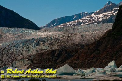 Hikers view of blue skies and icebergs and cliffs and Mendenhall Lake framing Mendenhall Glacier within Tongass National Forest (USA Alaska Juneau)