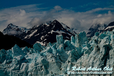 Blue skies and cotton candy clouds over steely blue Margerie Glacier and Tarr Inlet and Mount Forde within Glacier Bay National Park and Preserve (USA AK Gustavus)