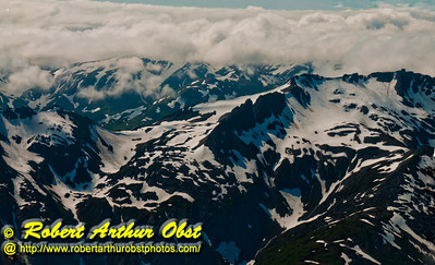 Cotton candy clouds embrace snowy Coast Mountains and Amherst Peak near Mendenhall Glacier within the Tongass National Forest (USA Alaska Juneau)