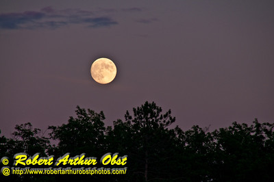 Full harvest moon with sunset after glow radiating pink over Waubee Lake from Waubee Lodge (USA WI Lakewood)