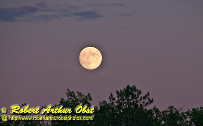 Full moon rising in clear northeastern WI skies radiating with pink sunset after glow over Waubee Lake near Waubee Lodge (USA WI Lakewood)